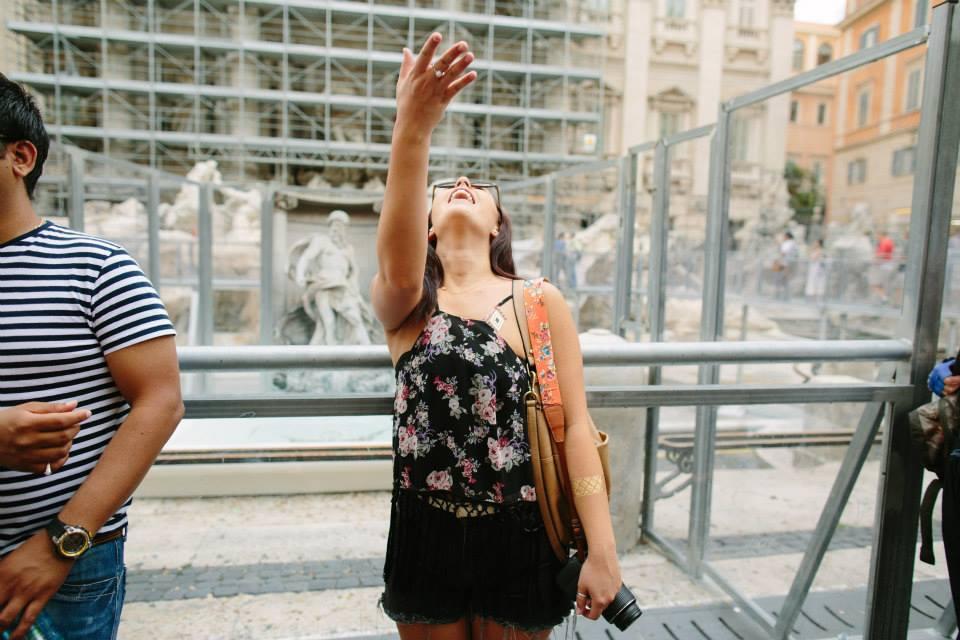 ASHTON THROWING A COIN INTO THE TREVI FOUNTAIN IN ROME