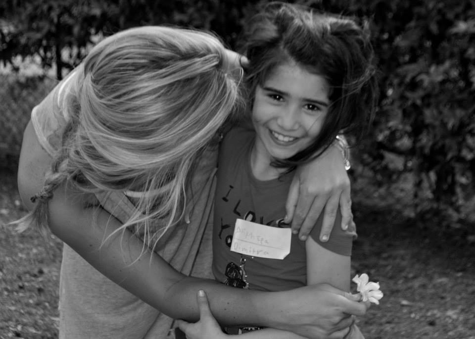 BONNIE SHARING A SWEET MOMENT WITH A CHILD IN GREECE.